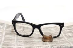 Σπασμένα γυαλιά και νόμισμα στην έκθεση αποθεμάτων Στοκ Εικόνες