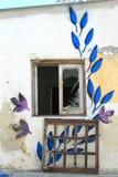 Σπασμένα εγκαταλειμμένα λουλούδια προσόψεων τοίχων σπιτιών παραθύρων γυαλί στοκ εικόνα με δικαίωμα ελεύθερης χρήσης