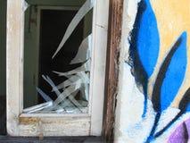 Σπασμένα εγκαταλειμμένα λουλούδια προσόψεων τοίχων σπιτιών παραθύρων γυαλί στοκ φωτογραφία με δικαίωμα ελεύθερης χρήσης
