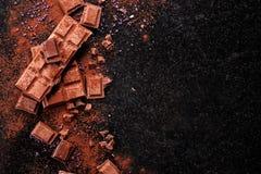 Σπασμένα κομμάτια σοκολάτας και σκόνη κακάου στο μάρμαρο Στοκ φωτογραφία με δικαίωμα ελεύθερης χρήσης