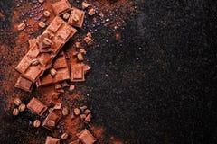 Σπασμένα κομμάτια σοκολάτας και σκόνη κακάου στο μάρμαρο Στοκ Φωτογραφίες