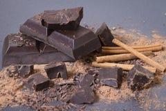 Σπασμένα κομμάτια της σκοτεινής κινηματογράφησης σε πρώτο πλάνο σοκολάτας γλυκό σοκολάτας ανασκό&p Ραβδιά σκονών και κανέλας κακά Στοκ εικόνα με δικαίωμα ελεύθερης χρήσης