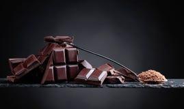 Σπασμένα μαύρα κομμάτια σοκολάτας και τσιπ σοκολάτας στο μικρό κουτάλι Στοκ εικόνες με δικαίωμα ελεύθερης χρήσης