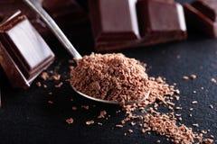 Σπασμένα μαύρα κομμάτια σοκολάτας και τσιπ σοκολάτας στο μικρό κουτάλι Στοκ φωτογραφία με δικαίωμα ελεύθερης χρήσης