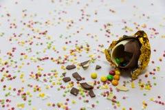 Σπασμένα χρυσά αυγά Πάσχας σοκολάτας με τις ζωηρόχρωμες σοκολάτες μέσα στο άσπρο υπόβαθρο με το ζωηρόχρωμο θολωμένο κομφετί στοκ εικόνες