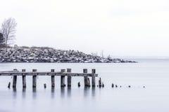 Σπασμένες ξύλινες θέσεις αποβαθρών μπροστά από τη δύσκολη ακτή με τον πάγκο, στοκ φωτογραφίες
