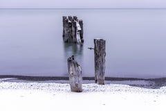 Σπασμένη αποβάθρα με δύο θέσεις στην ακτή που αποσυνδέεται από το Πε Στοκ φωτογραφία με δικαίωμα ελεύθερης χρήσης