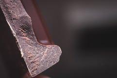 Σπασμένη μαύρη κινηματογράφηση σε πρώτο πλάνο σοκολάτας με τη σύσταση και το θολωμένο υπόβαθρο στοκ εικόνα