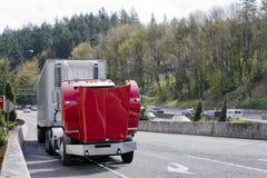 Σπασμένος στο κόκκινο ημι φορτηγό οδικών μεγάλο εγκαταστάσεων γεώτρησης με μια ανοικτή κουκούλα Στοκ Εικόνες