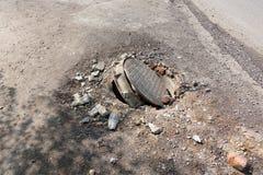 Σπασμένος υπόνομος στο δρόμο Κίνδυνος του τραυματισμού Επισκευή των επικοινωνιών στοκ φωτογραφίες