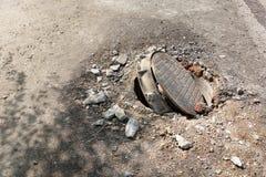 Σπασμένος υπόνομος στο δρόμο Κίνδυνος του τραυματισμού Επισκευή των επικοινωνιών στοκ εικόνες