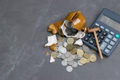 Σπασμένος piggy με τον υπολογιστή, νομίσματα, μάνδρα, έννοια σημειώσεων στον πίνακα Στοκ Φωτογραφία