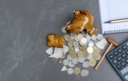 Σπασμένος piggy με τον υπολογιστή, νομίσματα, μάνδρα, έννοια σημειώσεων στον πίνακα Στοκ Εικόνες