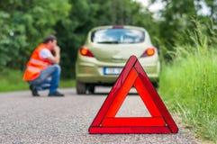 Σπασμένο αυτοκίνητο στο δρόμο και το δυστυχισμένο οδηγό Στοκ εικόνα με δικαίωμα ελεύθερης χρήσης