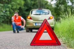 Σπασμένο αυτοκίνητο στο δρόμο και το δυστυχισμένο οδηγό Στοκ Εικόνες