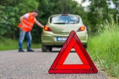Σπασμένο αυτοκίνητο στο δρόμο και το δυστυχισμένο οδηγό Στοκ εικόνες με δικαίωμα ελεύθερης χρήσης