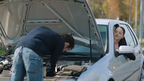 Σπασμένο επισκευή αυτοκίνητο ανδρών για μια γυναίκα απόθεμα βίντεο
