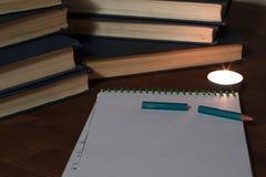Σπασμένο μολύβι και ένα κενό φύλλο του σημειωματάριου στο υπόβαθρο ενός σωρού των βιβλίων και ενός κεριού Στοκ φωτογραφία με δικαίωμα ελεύθερης χρήσης
