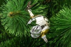 Σπασμένο παιχνίδι Χριστουγέννων σε ένα υπόβαθρο χριστουγεννιάτικων δέντρων Στοκ Φωτογραφία