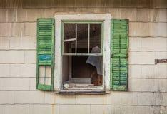 Σπασμένο παράθυρο με τα πράσινα παραθυρόφυλλα στην παλαιά αγροτική εγκαταλειμμένη σιταποθήκη που περιβάλλεται από το φωτεινό φύλλ Στοκ φωτογραφία με δικαίωμα ελεύθερης χρήσης