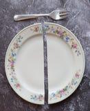 Σπασμένο πιάτο με ένα δίκρανο στην γκρίζα επιφάνεια Στοκ Εικόνα