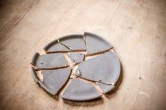 Σπασμένο πιάτο που βρίσκεται σε έναν ξύλινο πίνακα Στοκ Φωτογραφία
