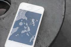 Σπασμένο τηλέφωνο στο πάτωμα, τηλέφωνο ζημίας στο πάτωμα Στοκ Φωτογραφία