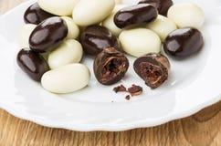 Σπασμένο φασόλι κακάου στη μαύρη σοκολάτα στο πιάτο Στοκ Φωτογραφίες