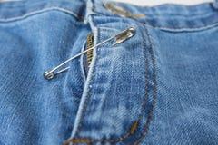 Σπασμένο φερμουάρ τζιν παντελόνι που καθορίζεται με την καρφίτσα ασφάλειας Στοκ εικόνες με δικαίωμα ελεύθερης χρήσης