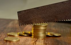 Σπαταλώντας την έννοια χρημάτων με την κοπή των χρυσών νομισμάτων Στοκ φωτογραφία με δικαίωμα ελεύθερης χρήσης