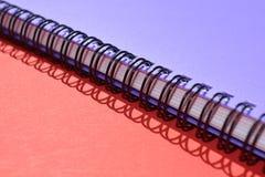 Σπείρα - συνδεδεμένο σημειωματάριο, λεπτομέρεια, στο κόκκινο υπόβαθρο στοκ φωτογραφία