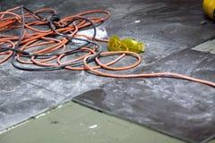 Σπείρες του ηλεκτρικού καλωδίου που βρίσκεται στον εργασιακό χώρο πατωμάτων Στοκ Εικόνες
