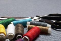 Σπείρες του νήματος των διαφορετικών χρωμάτων σε ένα γκρίζα υπόβαθρο και ένα ψαλίδι υφάσματος στοκ φωτογραφία με δικαίωμα ελεύθερης χρήσης