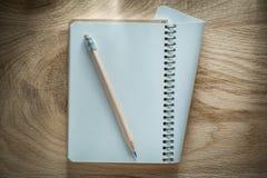 Σπειροειδές μολύβι σημειωματάριων στην ξύλινη έννοια γραφείων πινάκων Στοκ Εικόνες