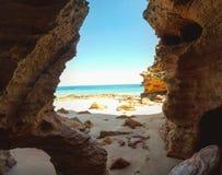 Σπηλιά που ανοίγει επάνω σε μια παραλία Στοκ φωτογραφία με δικαίωμα ελεύθερης χρήσης