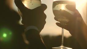 Σπινθηρίσματα και αφροί CHAMPAGNE στον ήλιο ερωτευμένα γυαλιά κρασιού εκμετάλλευσης ζευγών με το λαμπιρίζοντας κρασί στο υπόβαθρο φιλμ μικρού μήκους