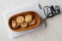 Σπιτικά αλμυρά μπισκότα γιαουρτιού με τις κυλημένες βρώμες/αλατισμένες ζύμες στο ξύλινο κύπελλο στοκ φωτογραφίες