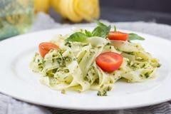 Σπιτικά ζυμαρικά από το βασιλικό και arugula με το πράσινο pesto σε ένα άσπρο πιάτο σε ένα σκοτεινό υπόβαθρο carpaccio κουζίνας ά Στοκ φωτογραφία με δικαίωμα ελεύθερης χρήσης