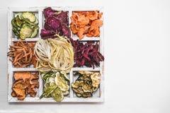 Σπιτικά ζωηρόχρωμα τσιπ των διαφορετικών φρέσκων λαχανικών σε ένα άσπρο ξύλινο κιβώτιο σε ένα άσπρο υπόβαθρο διάστημα αντιγράφων  Στοκ Φωτογραφία