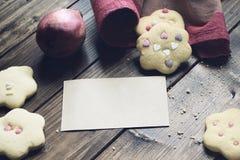 Σπιτικά διακοσμημένα μπισκότα με την κάρτα εγγράφου στον ξύλινο πίνακα Στοκ Εικόνες