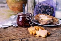 Σπιτικά μπισκότα μελιού ζάχαρης, μαρμελάδα σμέουρων στο βάζο, ψωμί και βούτυρο, μαχαίρι, σε ένα ξύλινο υπόβαθρο αυγό φλυτζανιών έ Στοκ Εικόνες
