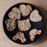 Σπιτικά μπισκότα με μορφή μιας καρδιάς και μιας γάτας, oatmeal ζύμες στο Μαύρο γύρω από το πιάτο σε ένα μπεζ υπόβαθρο στοκ φωτογραφία