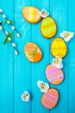 Σπιτικά μπισκότα με την τήξη με μορφή ενός αυγού για Πάσχα Εύγευστα μπισκότα Πάσχας σε ένα μπλε υπόβαθρο Χρωματισμένο λούστρο Στοκ Εικόνες