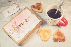 Σπιτικά μπισκότα, μορφή καρδιών, μαύρος καφές και αγάπη παρόντες στοκ εικόνες