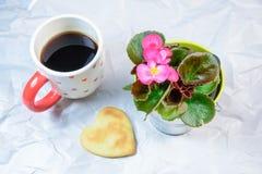 Σπιτικά μπισκότα, μορφή καρδιών, Begonia και ένα φλυτζάνι του μαύρου καφέ στοκ φωτογραφίες με δικαίωμα ελεύθερης χρήσης