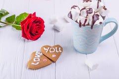 Σπιτικά μπισκότα στη μορφή της καρδιάς με την αγάπη εσείς που γράφετε στον άσπρο ξύλινο πίνακα με το ροδαλό λουλούδι και το φλυτζ Στοκ Εικόνες