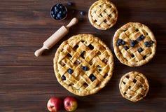 Σπιτικά προϊόντα αρτοποιίας πιτών μήλων ζύμης στο σκοτεινό ξύλινο πίνακα κουζινών με τις σταφίδες και τα μήλα Παραδοσιακό επιδόρπ Στοκ εικόνα με δικαίωμα ελεύθερης χρήσης