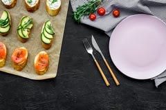 Σπιτικά σάντουιτς με το γαλλικούς baguette, το σολομό, το τυρί και το λαχανικό στο μαύρο πρότυπο άποψης υποβάθρου τοπ Στοκ Εικόνα