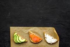 Σπιτικά σάντουιτς με το γαλλικούς baguette, το σολομό, το τυρί και το λαχανικό στο μαύρο πρότυπο άποψης υποβάθρου τοπ Στοκ Εικόνες