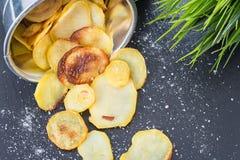 Σπιτικά τσιπ πατατών με το άλας θάλασσας στο σκοτεινό υπόβαθρο Στοκ Φωτογραφία